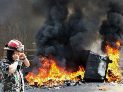 A Lebanese firefighter walks past a burning dumpster during a demonstration in central Beirut's Martyr Square on September 29, 2019. - Hundreds of people protested in Lebanon's capital today over increasingly difficult living conditions, amid fears of a dollar shortage and possible price hikes. (Photo by ANWAR AMRO / AFP) …