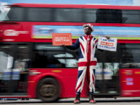 A pro-Brexit campaigner wears the Union flag colours and holds placards as he demonstrates near the Houses of Parliament in central London on April 3, 2019. - Prime Minister Theresa May was to meet on Wednesday with the leader of Britain's main opposition party in a bid to thrash out …