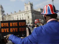 Pro-Brexit activist Joseph Afrane holds a placard as he demonstrates outside the Houses of Parliament in Westminster, London on March 28, 2019. - Faced with losing all control over the Brexit process, British Prime Minister Theresa May looks to have played her final card by announcing she will step down …