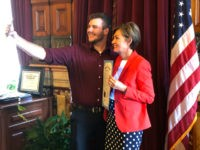 Carson King, of Altoona, Iowa, snaps a selfie Wednesday, Sept. 25, 2019, in the Iowa State Capitol in Des Moines, Iowa, with Iowa Gov. Kim Reynolds, who holds a proclamation declaring Saturday as Carson King Day. The honor was to mark King's plans to donate more than $1 million to …