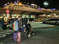 A passenger from the Royal Caribbean cruise ship, Anthem of the Seas, adjusts her luggage after disembarking from the ship upon arriving at Cape Liberty cruise port, Wednesday, Feb. 10, 2016, in Bayonne, N.J. Carrying 4,500 passengers and 1,600 crew members, the ship returned early from a seven-day cruise to …