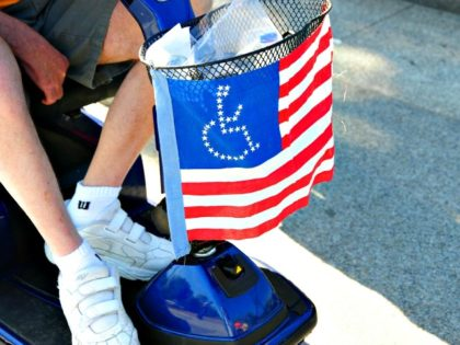 A member of ADAPT, a disability rights group, passes the White House during a protest April 27, 2009 in Washington, DC. The group is calling on US President Barack Obama to pass the Community Choice Act, a community-based alternative to nursing homes and institutions for people with disabilities AFP PHOTO/Karen …