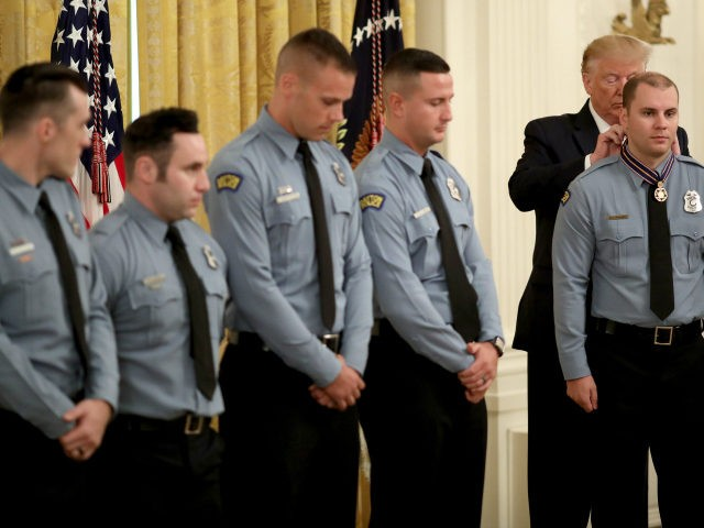 U.S. President Donald Trump presents the Medal of Valor to Officer Brian Rolfes of the Dayton Police Department during a White House ceremony September 9, 2019 in Washington, DC. Rolfes was presented with the honor along with Officer Jeremy Campbell, Sgt. William Knight , Officer Vincent Carter, Officer Ryan Nabel …