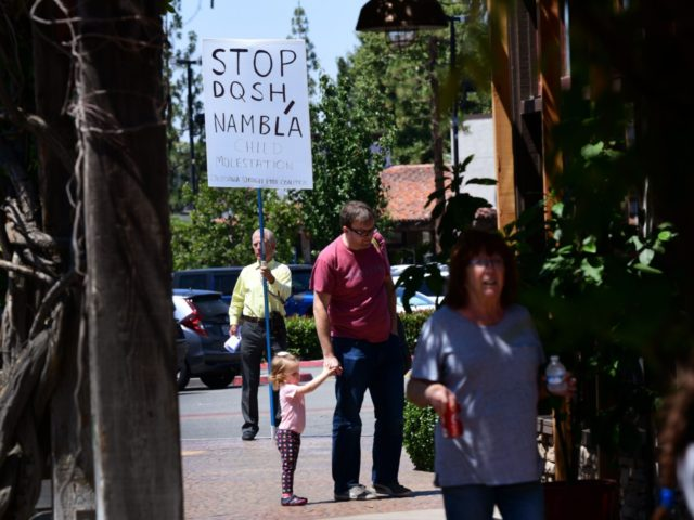 A protestor holds a sign while keeping his distance from the bookstore where drag queens read to adults and children during Drag Queen Story Hour at Cellar Door Books in Riverside, California on June 22, 2019. - Athena and Scalene, their long blonde hair flowing down to their sequined leotards …