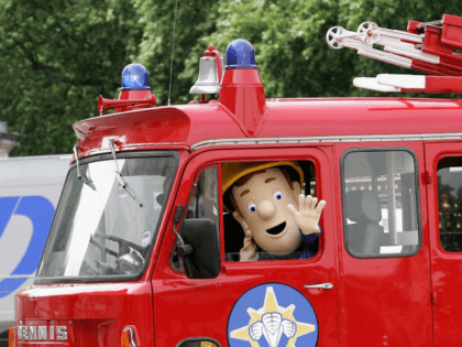 LONDON - JUNE 25: Fireman Sam arrives in his fire engine on the Forecourt of Buckingham Palace for the Queen's 80th Birthday - Children's Garden Party on June 25, 2006 in London. (Photo by Gareth Cattermole/Getty Images)