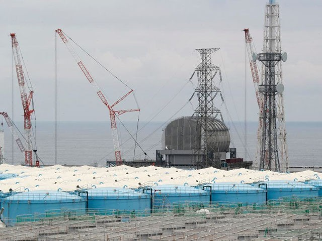 This picture taken on July 27, 2018 and made available on July 30, 2018 shows reactor unit 3 over storage tanks of radiation-contaminated water at the tsunami-crippled Tokyo Electric Power Company (TEPCO) Fukushima Dai-ichi nuclear power plant in Okuma, Fukushima prefecture. - The Fukushima nuclear disaster was triggered by a …