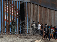 Central American migrants look through a border fence as a US Border PatRol agents stands guard near the El Chaparral border crossing in Tijuana, Baja California State, Mexico, on November 25, 2018. - Hundreds of migrants attempted to storm a border fence separating Mexico from the US on Sunday amid …