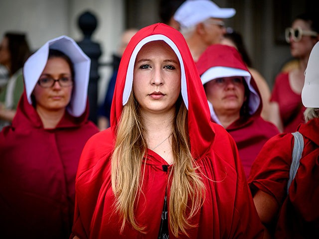 Handsmaid themed protesters stand outside Jackson Square in the French Quarter of New Orleans, Louisiana, on May 25, 2019, to protest the proposed Heartbeat Bill that will ban abortion after 6 weeks in that state scheduled for a vote on May 28. (Photo by Emily KASK / AFP) (Photo credit …