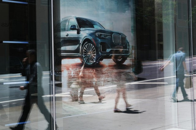 NEW YORK, NEW YORK - JUNE 11: People walk by a car dealership in Manhattan on June 11, 2019 in New York City. Disrupted by technology, a young generation indifferent to auto ownership, car hailing services and a resurgence in urban cycling, global auto sales are slipping for the first …