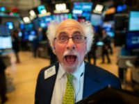 A traders jokes after the opening bell at the New York Stock Exchange (NYSE) on July 16, 2019 located at Wall Street in New York City. - Wall Street stocks edged down from records early Tuesday following mixed banking earnings and worrisome manufacturing data contrasted with strong US retail sales. …