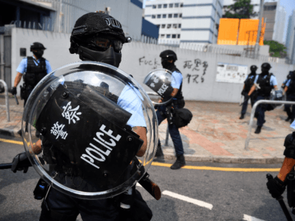 Riot police protect a police station from protesters at Kowloon Bay in Hong Kong on August 24, 2019, in the latest opposition to a planned extradition law that has since morphed into a wider call for democratic rights in the semi-autonomous city. - Hong Kong riot police on August 24, …