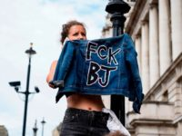 "A protester holds up her jacket during a demonstration against the British government's move to suspend parliament in the final weeks before Brexit outside Downing Street in London on August 31, 2019. - Demonstrations, being dubbed ""Stop The Coup"" by organisers, were to be held across Britain on August 31 …"