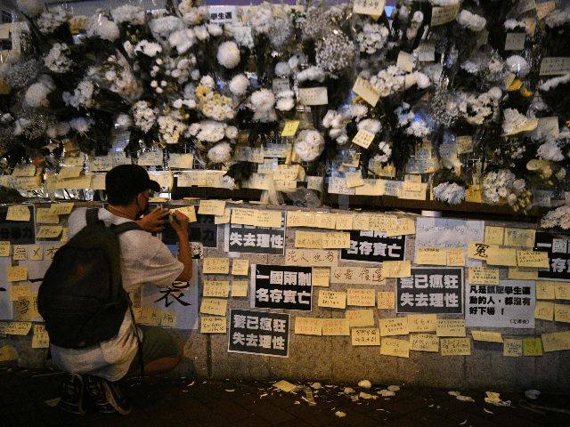 A man writes a note amongst flowers left outside the Prince Edward MTR underground train station in Hong Kong on September 4, 2019, for protesters who were injured during police arrests on August 31. - Hong Kong's leader on September 4, 2019 bowed to a key demand of pro-democracy protesters …