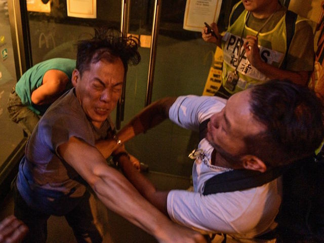 Two people broke into a fight during a protest in Hong-Kong on September 15, 2019. - Hong Kong riot police fired tear gas and water cannons at hardcore pro-democracy protesters hurling rocks and petrol bombs on September 15, tipping the violence-plagued city back into chaos after a brief lull in clashes. (Photo by Nicolas ASFOURI / AFP) (Photo credit should read NICOLAS ASFOURI/AFP/Getty Images)