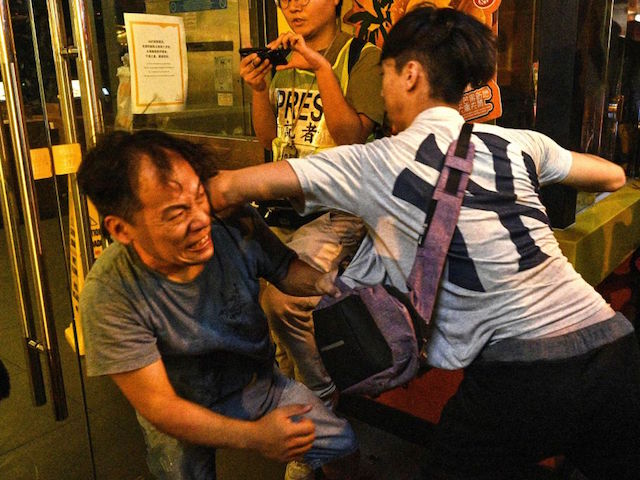TOPSHOT - Two men fight on a street in North Point in Hong Kong on September 15, 2019. - Hong Kong riot police fired tear gas and water cannon at hardcore pro-democracy protesters hurling rocks and petrol bombs on September 15, tipping the violence-plagued city back into chaos after a brief lull in clashes. (Photo by Anthony WALLACE / AFP) (Photo credit should read ANTHONY WALLACE/AFP/Getty Images)