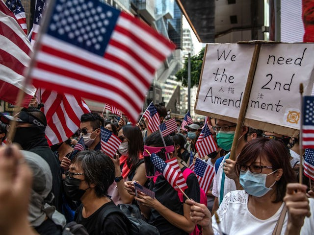 HONG KONG, CHINA - SEPTEMBER 15: Protesters wave U.S flags as they gather ahead of a pro-democracy march on September 15, 2019 in Hong Kong, China. Pro-democracy protesters have continued demonstrations across Hong Kong, calling for the city's Chief Executive Carrie Lam to immediately meet the rest of their demands, including an independent inquiry into police brutality, the retraction of the word 'riot' to describe the rallies, and genuine universal suffrage, as the territory faces a leadership crisis. (Photo by Carl Court/Getty Images)