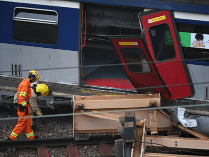 Rescue workers investigate the scene of a passenger train that derailed during the rush hour outside Hung Hom railway station on the Kowloon side of Hong Kong on September 17, 2019. - A passenger train derailed during the morning rush hour in Hong Kong on September 17 leaving eight people …