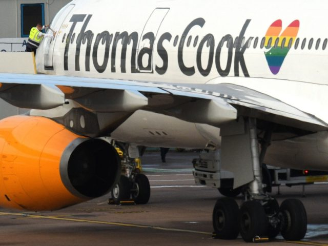 A worker closes the door of a Thomas Cook passenger aircraft after it landed at Manchester Airport in Manchester, northern England on Septmeber 23, 2019. - British travel group Thomas Cook on Monday declared bankruptcy after failing to reach a last-ditch rescue deal, triggering the UK's biggest repatriation since World …