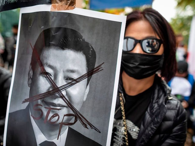 A protestor holds a portrait of Xi Jinping - General Secretary of the Communist Party of China as they demonstrate in front of China embassy in Warsaw in support of pro democracy protests in Hong Kong, September 29, 2019. (Photo by Wojtek RADWANSKI / AFP) (Photo credit should read WOJTEK …