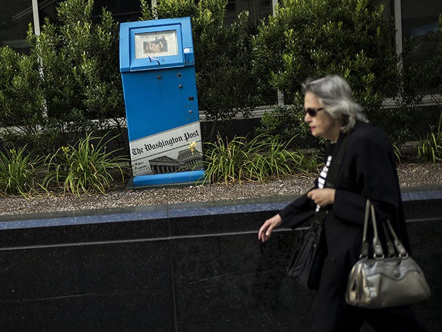 A woman walks past a Washington Post newspaper box outside the Washington Post on August 5, 2013 in Washington, DC after it was announced that Amazon.com founder and CEO Jeff Bezos had agreed to purchase the Post for USD 250 million. Multi-billionaire Bezos, who created Amazon, which has soared in …