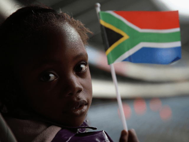 A girl waves a South African flag while watching the official memorial service for Nelson Mandela on a large screen inside the Orlando Stadium in Soweto, on December 10, 2013 in Johannesburg, South Africa. Over 60 heads of state have travelled to South Africa to attend a week of events …