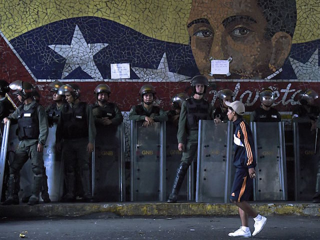 Security forces stand guard near Miraflores presidential palace where people protest against the severe food and medicine shortages, in Caracas on June 2, 2016. Venezuelans face long lines at supermarkets tightly guarded by nervous soldiers, bare shelves and soaring prices inside, a dysfunctional health care system short on basic medications …