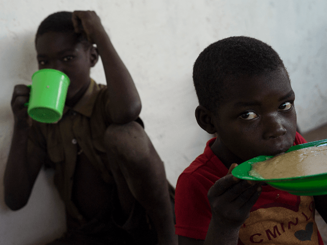 Children eat porridge, locally known as Uji, as the WFP, The 'World Food Programme' distribute hot meals at the Imvepi Settlement on February 23, 2017 in Imvepi, Uganda. The continuing flow of refugees from South Sudan is putting pressure on the many humanitarian partners and their capacity to cope with …