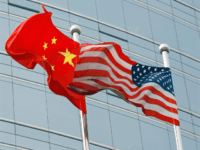 "A US and a Chinese flag wave outside a commercial building in Beijing, 09 July 2007. US Secretary of State Condoleezza Rice 06 July 2007 accused China of flouting the rules of global trade in its headlong economic expansion as the US administration ""has not been hesitant"" to deploy trade …"