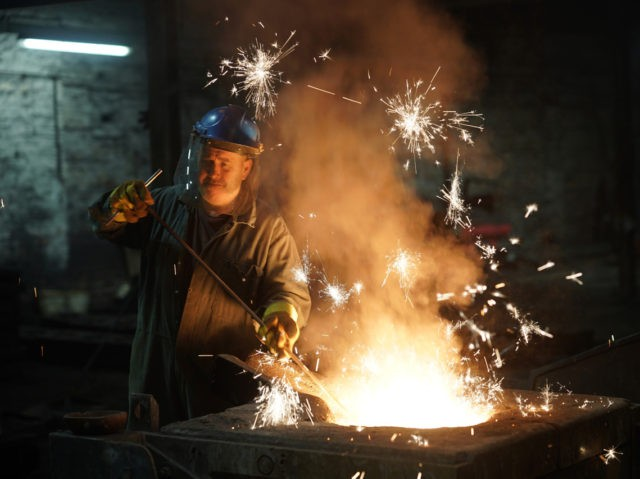WALSALL, ENGLAND - FEBRUARY 21: Furnace man Paul Taylor tends the iron furnace at Kirkpatrick Foundry on February 21, 2018 in Walsall, England. Kirkpatrick Ltd is the oldest established manufacturer of black iron door and window furniture in the UK. The Black Country factory is the only manufacturer of traditional …