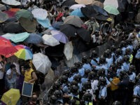 Pro-democracy protesters hold umbrellas and wear protective clothing in front of a police line near the government headquarters in Hong Kong on September 28, 2014. Police fired tear gas as tens of thousands of pro-democracy demonstrators brought parts of central Hong Kong to a standstill Sunday, in a dramatic escalation …