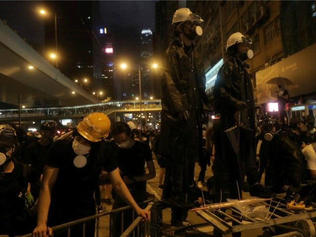 Protesters stand on improvised barricades after a march against a controversial extradition bill in Hong Kong on July 21, 2019. - Masked protesters threw eggs at China's office in Hong Kong on July 21 following another massive rally, focusing anger towards the embodiment of Beijing's rule with no end in …