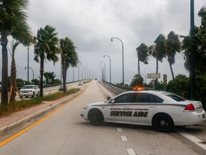 Authorities block a road in Jensen Beach, Florida on September 2, 2019. - Monster storm Dorian came to a near stand-still over the Bahamas, prolonging the agony as surging seawaters and hurricane winds made a shambles of low-lying island communities and spurred mass evacuations along the US east coast. It …