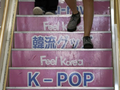 In this Aug. 13, 2019 photo, visitors walk down the stairs at a shop selling South Korean goods in Shin Okubo area in Tokyo. Tokyo's Shin Okubo district bustles with Korean restaurants and stores selling K-pop merchandise. (AP Photo/Eugene Hoshiko)