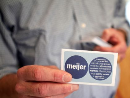 """DETROIT, MI - MAY 18: A man at a """"Groceries For Guns"""" gun buyback program displays a $50 Meijer gift card that people were given in exchange for guns they brough in May 18, 2013 at the New St. Paul Tabernacle Church of God in Christ in Detroit, Michigan. The …"""