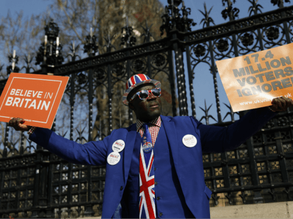Pro-Brexit activist Joseph Afrane holds placards as he demonstrates outside the Houses of Parliament in Westminster, London on March 28, 2019. - Faced with losing all control over the Brexit process, British Prime Minister Theresa May looks to have played her final card by announcing she will step down if …