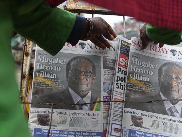 A man buys a daily newspaper at a stand on the streets of Nairobi, on September 7, 2019, following the death of former Zimbabwe president Robert Mugabe, guerrilla hero turned despot who ruled Zimbabwe for 37 years. - Mugabe, 95, passed away on September 6, 2019 in Singapore, where he …