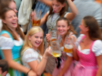 Young women in traditional Bavarian dress raise their beer glasses in a beer tent at the Oktoberfest beer festival in Munich, southern Germany, on September 22, 2019. - The world's biggest beer festival Oktoberfest will be running until October 6, 2019. (Photo by Tobias SCHWARZ / AFP) (Photo credit should …