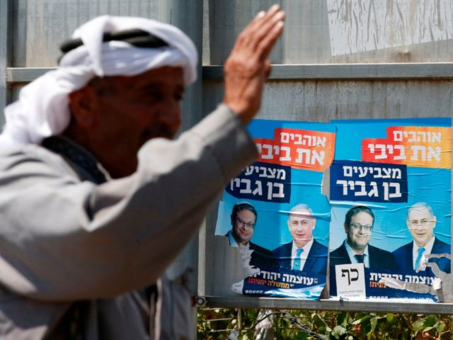A Palestinian gestures next to electoral campaign posters depicting Israeli Prime Minister Benjamin Netanyahu and far right politician Itamar Ben Gvir (L) in the West Bank town of Hebron on September 7, 2019. - Hebron is holy to both Muslims and Jews and has been a flashpoint in the Israeli-Palestinian …