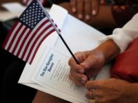 FILE - In this Aug. 16, 2019, file photo a citizen candidate holds an American flag and the words to The Star-Spangled Banner before the start of a naturalization ceremony at the U.S. Citizenship and Immigration Services Miami field office in Miami. U.S. Citizenship and Immigration Services officers can now …