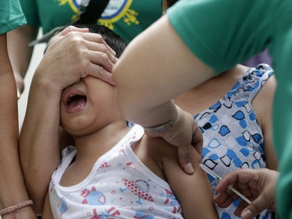 A local health worker administers a vaccine at a local health center at the financial district of Makati, east of Manila, Philippines, Friday, Sept. 12, 2014. The World Health Organization and the British government are working with the Philippine Department of Health, UNICEF and a host of other partners to …