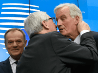 President of the European Commission Jean-Claude Juncker (C) kisses EU chief Brexit negotiator Michel Barnier (R) next to European Council President Donald Tusk (L) at the end of a press conference following a special meeting of the European Council to endorse the draft Brexit withdrawal agreement and to approve the …