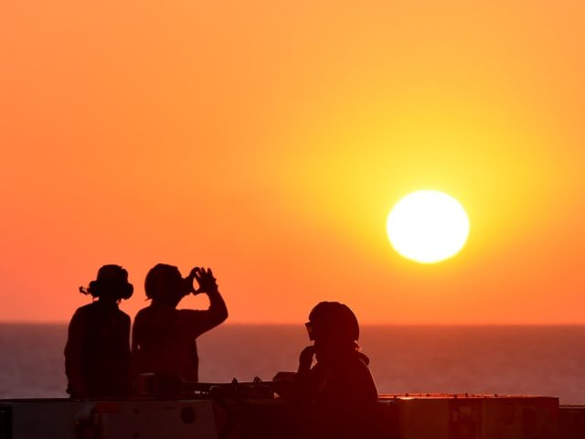 "Sailors look at sunset on the US navy's super carrier USS Dwight D. Eisenhower (CVN-69) (""Ike"") in the Mediterranean Sea on July 6, 2016. The US aircraft carrier is deployed in support of Operation Inherent Resolve, maritime security operations and theater security cooperation efforts in the US 6th Fleet area …"