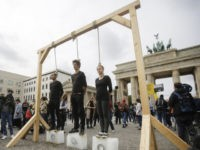 Three persons stand on ice blocks under gallows to protest against the climate policy (AP Photo/Markus Schreiber)