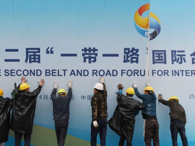 Workers take down a Belt and Road Forum panel outside the venue of the forum in Beijing on April 27, 2019. - Chinese President Xi Jinping urged dozens of world leaders on April 27 to reject protectionism and invited more countries to participate in his global infrastructure project after seeking …