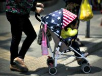File picture of a woman pushing a child in a stroller, adorned with colours of the US national flag, along a street in Shanghai (AFP Photo/Johannes EISELE)