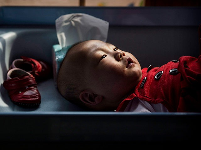 BEIJING, CHINA - APRIL 02: A young orphaned Chinese girl lays on a changing table at a foster care center on April 2, 2014 in Beijing, China. China's orphanages and foster homes used to be filled with healthy girls, reflecting the country's one-child policy and its preference for sons. Now …