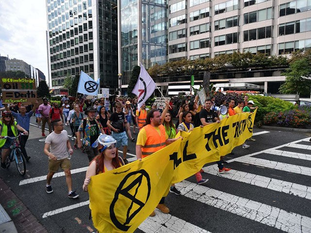 """Environmental activists block an intersection as they gather to protest to shut down the city during global climate action week on September 23, 2019 in Washington,DC. - Some 60 world leaders convene on Monday for a UN summit on """"climate emergency"""" aimed at reinvigorating the faltering Paris agreement, at a …"""
