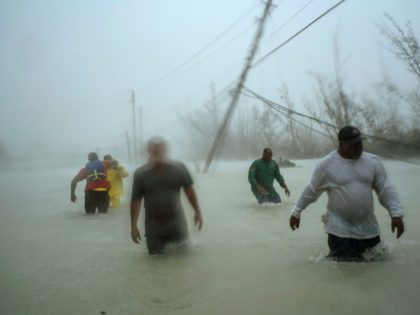 Volunteers walk under the wind and rain from Hurricane Dorian through a flooded road as they work to rescue families near the Causarina bridge in Freeport, Grand Bahama, Bahamas, Tuesday, Sept. 3, 2019. The storm's punishing winds and muddy brown floodwaters devastated thousands of homes, crippled hospitals and trapped people …