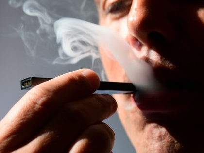An illustration shows a man exhaling smoke from an electronic cigarette in Washington, DC on October 2, 2018. - In just three years, the electronic cigarette manufacturer Juul has swallowed the American market with its vaporettes in the shape of a USB key. Its success represents a public health dilemma …