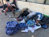 "In this photo taken July 25, 2019, sleeping people, discarded clothes and used needles sit across the street from a staffed ""Pit Stop"" public toilet in the Tenderloin neighborhood in San Francisco. Merchants say the bathrooms have given homeless and other people a private place to go so they don't …"